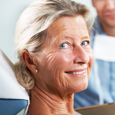 Older woman smiling from dental chair