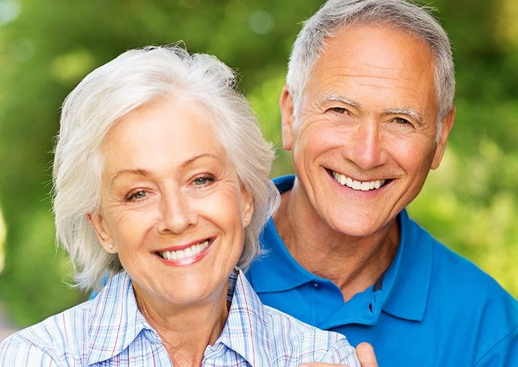 Dental Implants - Older couple smiling outside