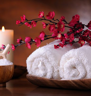 Two white towels with candles and flowers