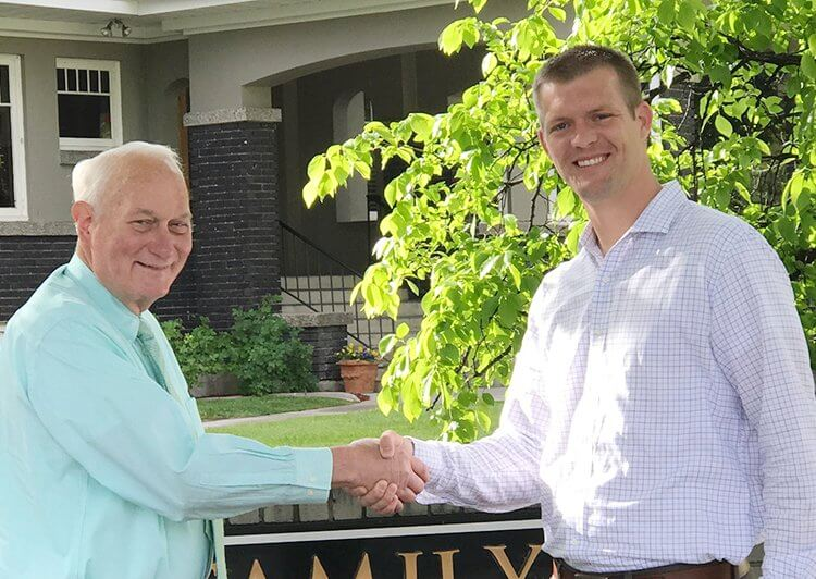 Dr. Tanner Hunsaker shaking hands with a man outside Midtown Dental in Logan, Utah