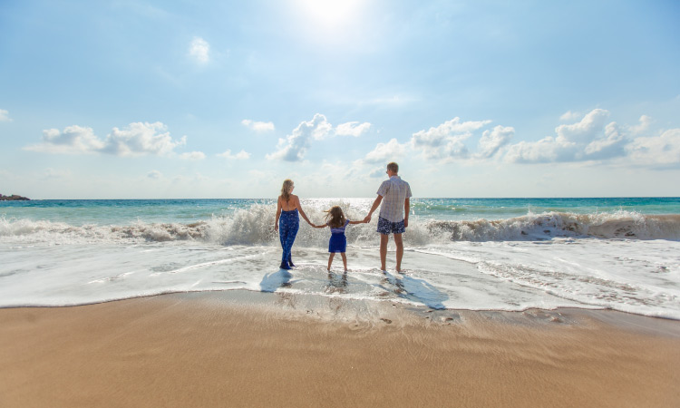 Mother, father, and daughter hold hands while standing in the shallow waves at the beach during summer vacation