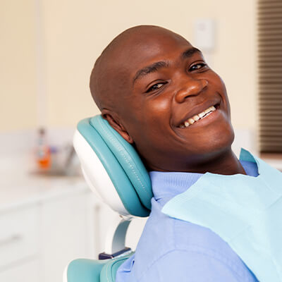 a man smiling as he sits in the dental chair