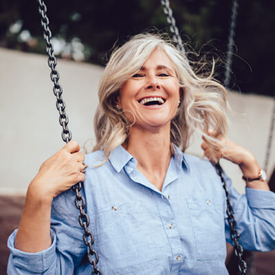 a woman with partial dentures smiling on a park swing