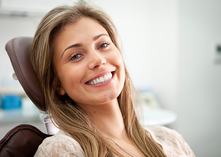 a woman sitting in a dental chair smiling after a successful root canal consult