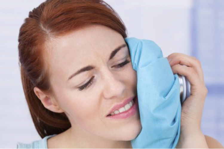 woman using an ice pack to sooth painful wisdom teeth