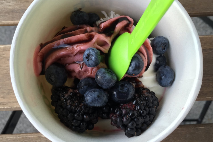 Aerial view of frozen yogurt with fresh berries and a green spoon