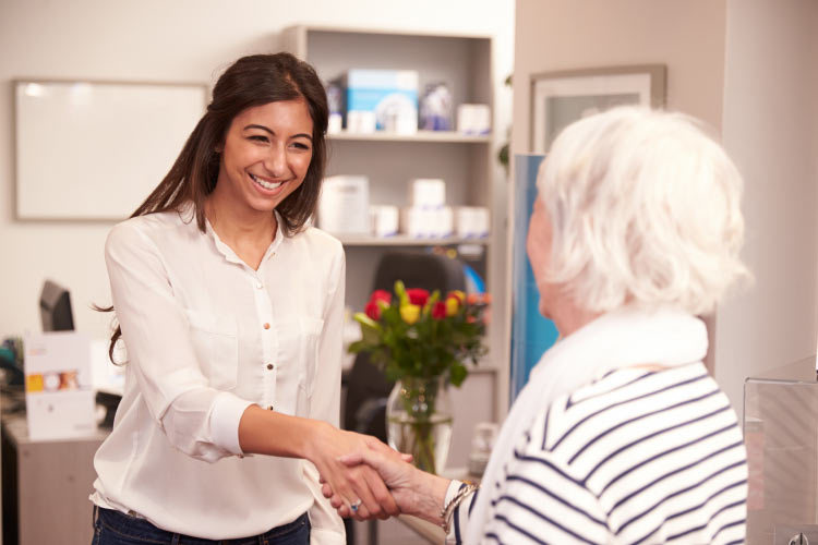 elderly patient being greeted at the dentist's front office