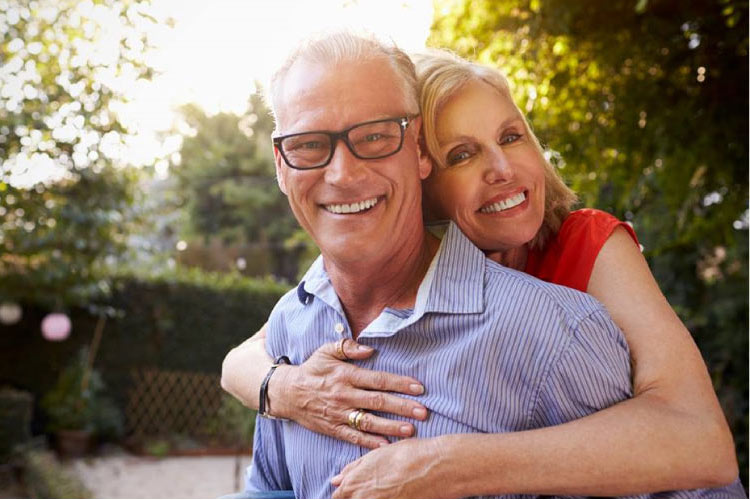 senior couple hugging and smiling after learning about the benefits of dentures