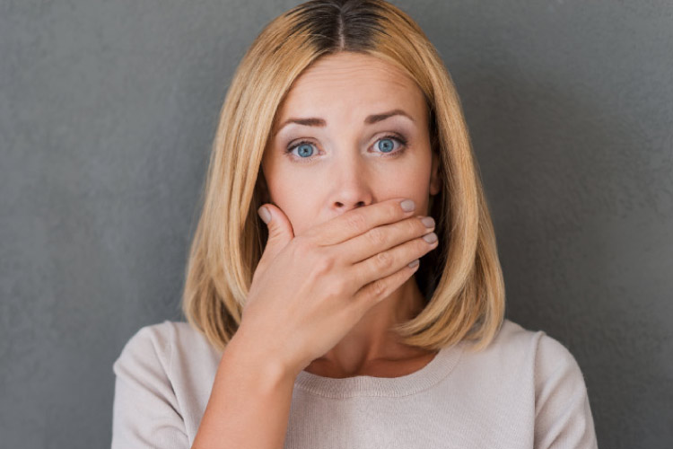 woman covers her mouth to hide her periodonal disease