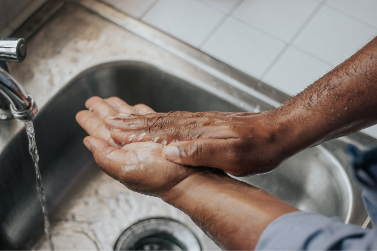 closeup of a man washing his hands with soap and water