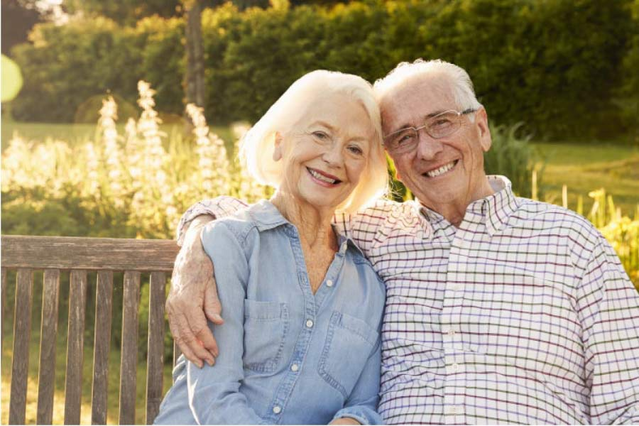 senior couple sitting on a bench hug and smile after learning how to adapt to dentures