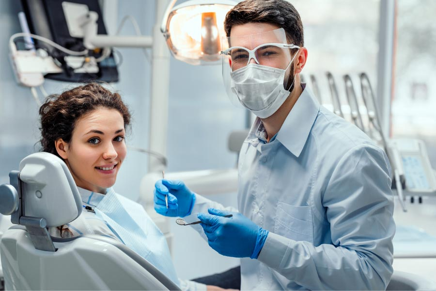 dentist wearing a mask puts a young patient at ease during her dental exam