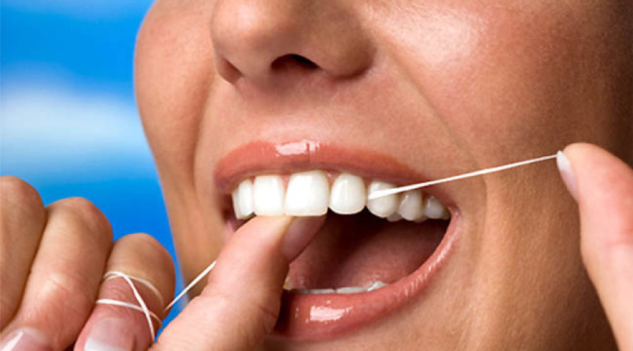 closeup of a woman flossing her teeth