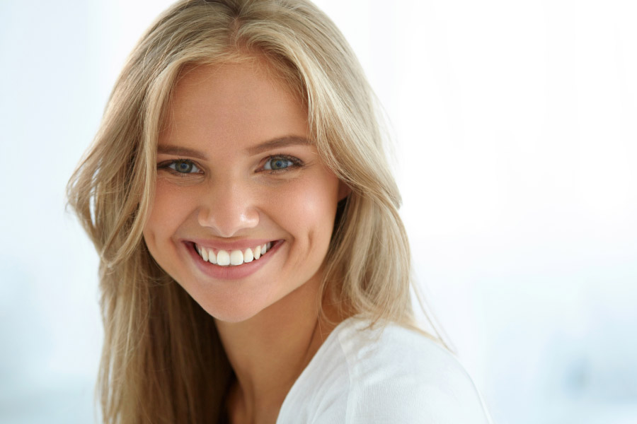young woman smiles showing off her white smile