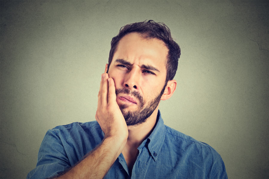 bearded man holds his jaw with pain from gum disease